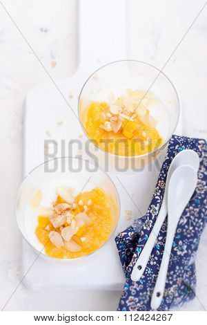 Sweet peach and pear compote with yogurt in a glass and jam