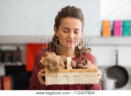 Woman With Her Eyes Closed Smelling Basket Of Fresh Mushrooms