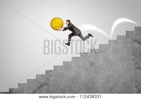 Businessman running down stairs holding big coin
