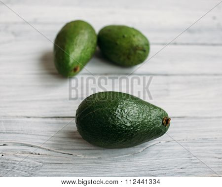 Three Avocados On A White Old Wooden Table