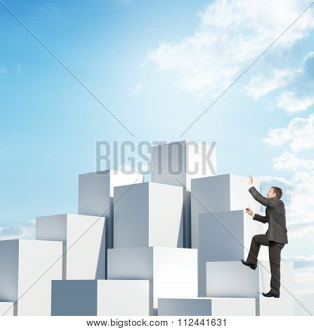 Businessman climbing boxes pile