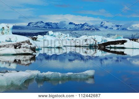 Sunrise. Blue and emerald icebergs and ice floes are reflected in smooth water of the Gulf Yokulsarlon in Iceland