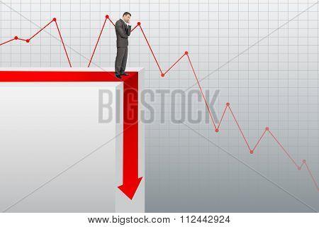 Sad businessman standing on edge of chart