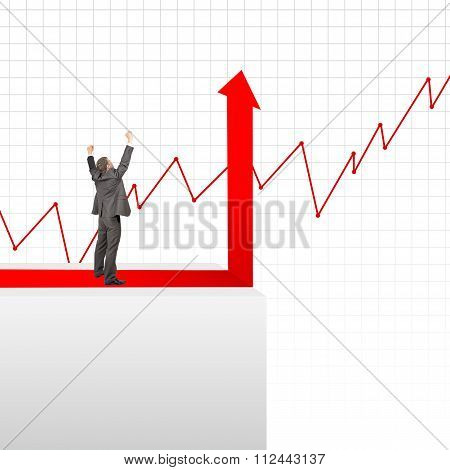 Happy businessman standing on edge of chart