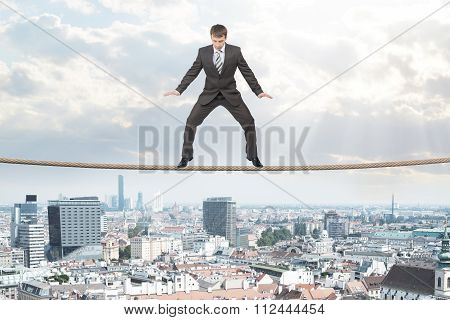 Businessman standing on rope