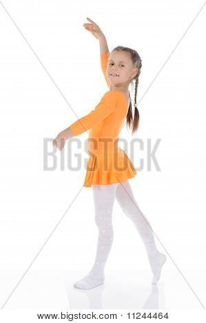 beautiful ballerina dancing in an orange dress.