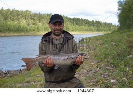 Fisherman caught a big salmon.