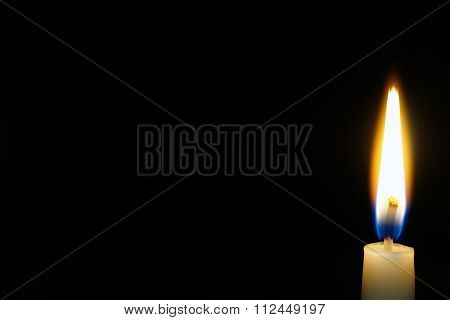 burning candle isolated on black