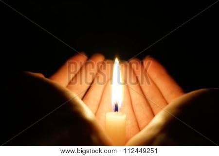 burning candle in the hands