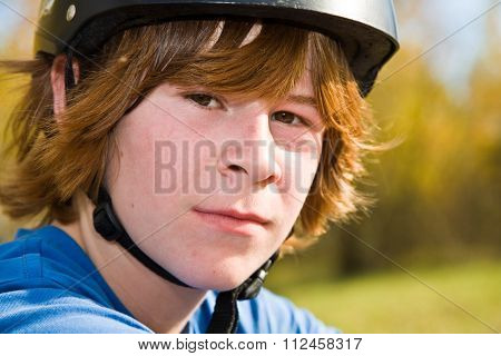 Portrait Of Boy With Red Long Hair And Helmet