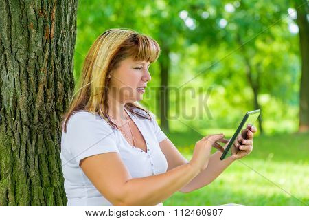 Portrait Of A Woman 50 Years Old With A Tablet In Her Hands In Park