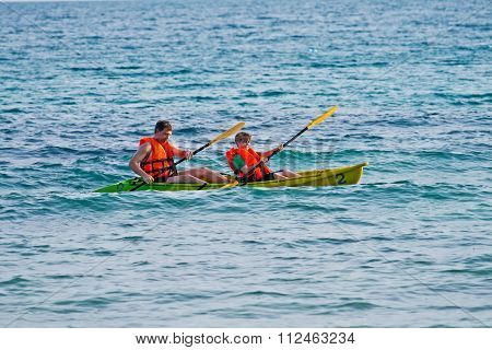 Father And Son Are Padelling With A Canoe On Open Sea