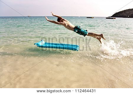 Young Boy With Red Hair In Swimsuit Is Running Along The Beautiful Beach And Enjoying It