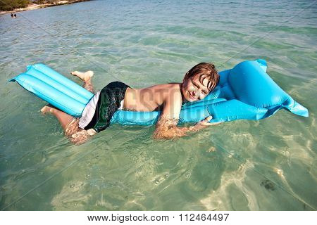 Boy With Red Hair Is Enjoying Jumping On The Air Mattress At The Crystal Clear Water At A Beautiful