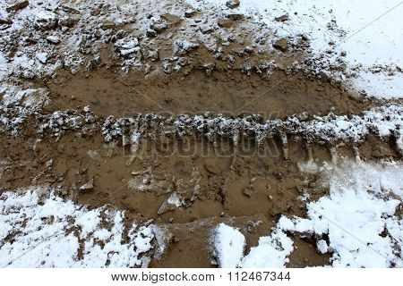 Wheel tracks on dirt and snow, impassable section of road