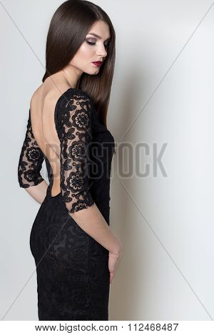 sexy beautiful elegant woman with long hair , bright evening make-up in a black evening dress in the