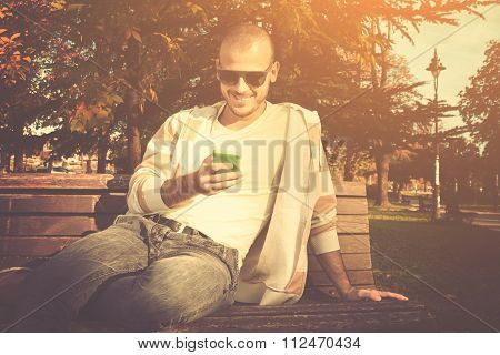 Urban guy texting on a bench in the park.