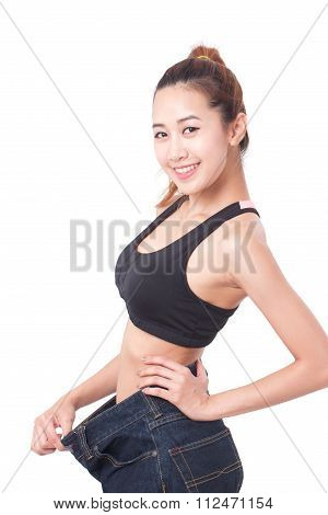 young slim woman wearing too big jeans on white background
