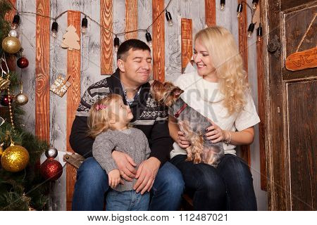 Happy Family Kissing With Dog At Home.