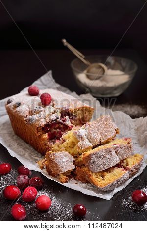 Cut Cranberry Muffin Against A Dark Background With Powdered Sugar And Cranberries