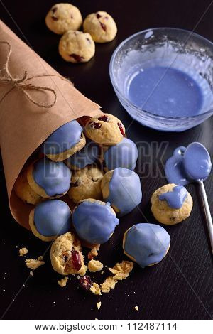 Cottage Cheese Cookies With Cranberries In A Blue Glaze And In Kraft Bag On A Dark Background