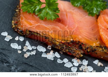 Smoked Salmon Slices And Seasoning On Natural Black Stone Background