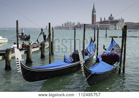 Tourist People And Gondolas Docked To The Poles On The Grand Canal
