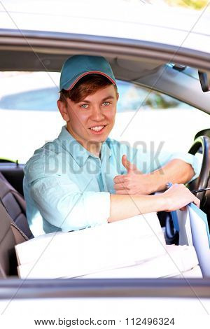 Pizza delivery boy in car, close-up