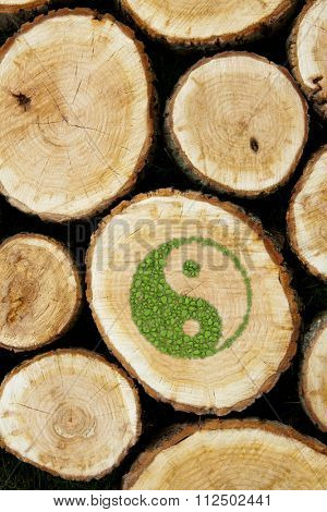 Stacked Logs Background with ying yang symbol of harmony.