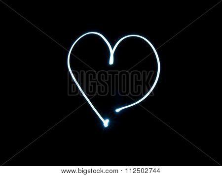 Light painting heart shape over black background