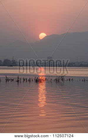 Golden Sunset At Ana Sagar Lake In Ajmer, India With Silhouettes Of Trees And Fisherman.