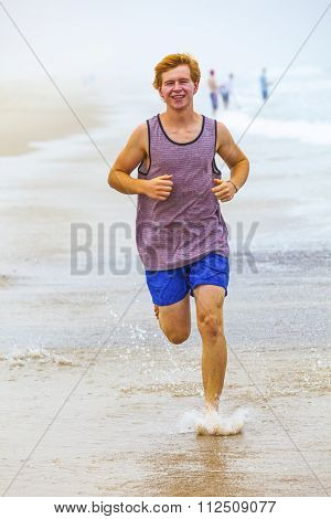 Attractive Boy Jogging Along The Beach In The Morning