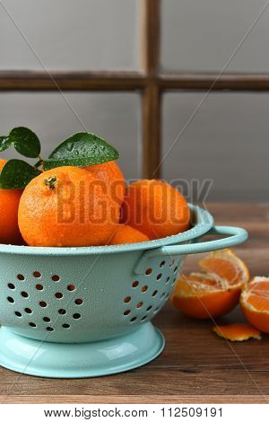 Closeup of fresh picked clementines in a colander in front of a window.