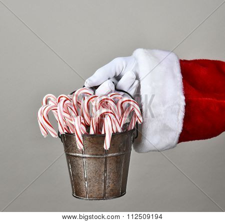 Closeup of Santa Claus hand holding a bucket filled with candy canes.