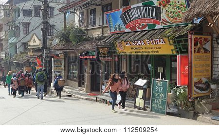 Visitors walking on a street with many restaurants in Sapa tourism town