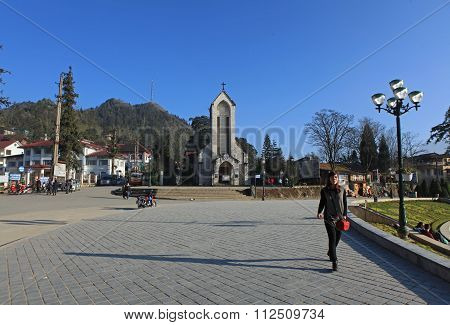 Travelers walking on the sidewalk of the square in front of the Catholic Holy Rosary church in Sapa