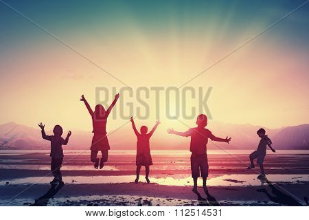 Silhouettes of group of children jumping high joyfully on sunset background