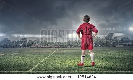 Rear view of kid boy in red uniform on soccer field