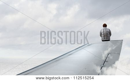 Middle aged stout woman sitting on edge of aairplane wing