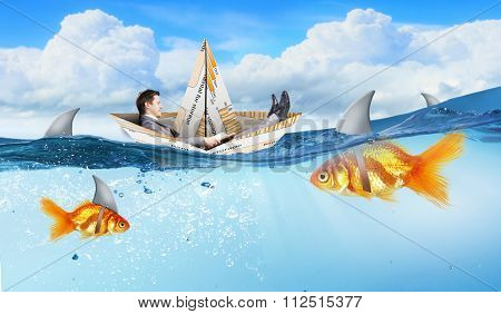 Concept of fake threat when businessman float in paper ship and sharks in water appear to be goldfish
