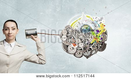 Young pretty businesswoman attaching tin phone to ear. Elements of this image are furnished by NASA