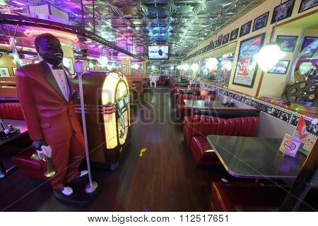 MOSCOW - JAN 21, 2015: Interior of the hall with leather red sofas and sculpture of a dark-skinned singer in the American restaurant Beverly Hills Diner