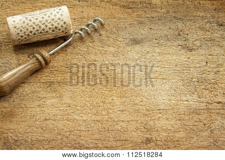 Wine Cork And Corkscrew On Wooden Table