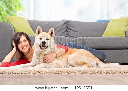 Young woman lying on the floor with her dog and hugging the dog by a gray couch at home shot with tilt and shift lens