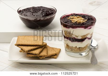 Healthy dessert with natural yogurt, full grain biscuits and black currant jam.
