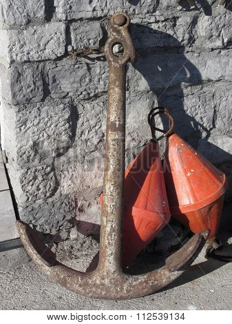 A Rusty Anchor And Two Orange Conical Buoys At The Marina