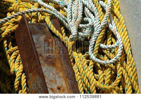 White and yellow rope and a piece of rusty metal