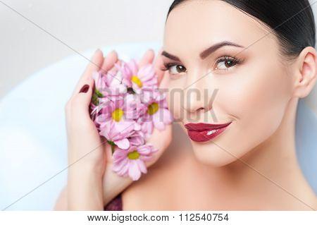 Cheerful young woman is enjoying herbal bathtub