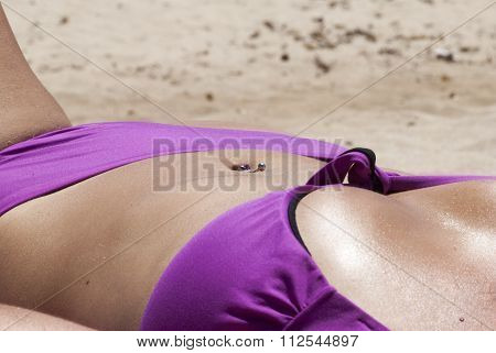 Female Body In Swimsuit Sunbathing With Pink Custom And Navel Piercing