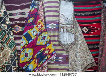 Various small carpets hanging outside souk.